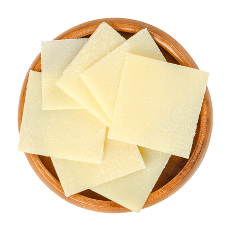 Parmesan cheese slices in wooden bowl. Parmigiano-Reggiano. Italian hard, granular cheese, of slightly yellow color, made of unpasteurized cow milk. Macro food photo, closeup, from above, over white.