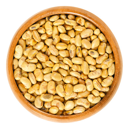 Roasted soybeans in wooden bowl. Dried, yellow soya beans, crispy roasted and slightly salted, used as snack. Rich in protein. Legume. Isolated macro food photo closeup from above on white background.