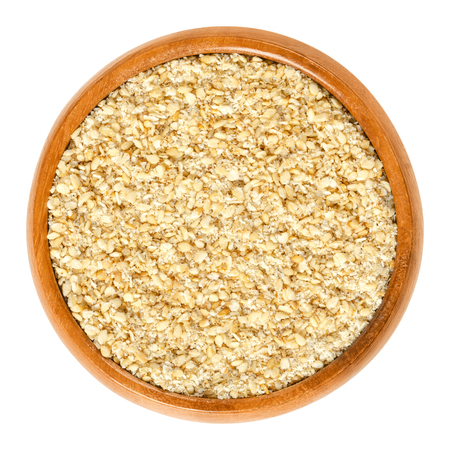 Gomashio in wooden bowl, also called gomasio. Dry condiment, made of toasted sesame seeds and salt, used in Japanese cuisine to sprinkle it over rice. Macro food photo closeup from above over white.