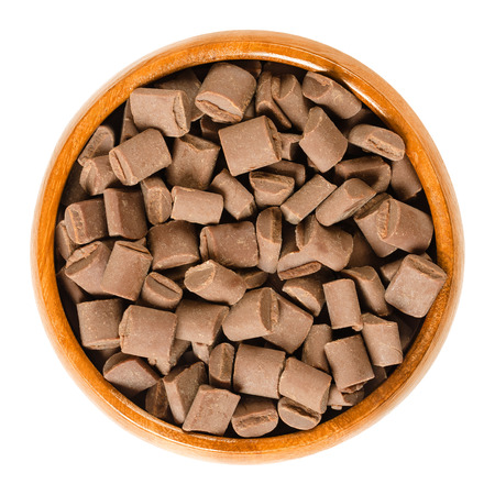 Chocolate chunks in wooden bowl. Milk chocolate pieces for baking and decorating of cookies, muffins and brownies. Edible baking igredient. Macro food photo closeup from above on white background. Stock Photo