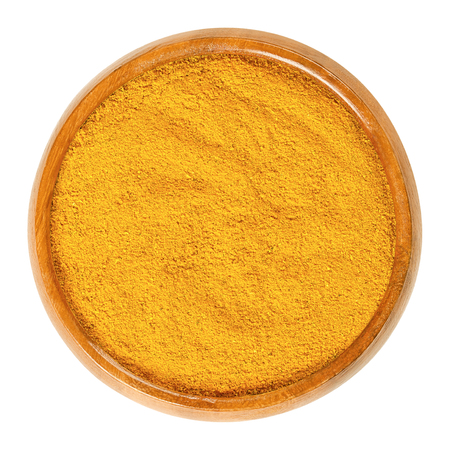 Curry powder in wooden bowl. Orange spice mix, made of different ingredients, most recipes include coriander, turmeric, curcuma, fenugreek, and chili peppers. Food photo closeup from above over white.