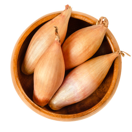 Whole long shallots in wooden bowl. Type of onion, Longor, French variety of Allium cepa with mild flavor. Brown, edible, raw, organic and vegan plant. Macro food photo, closeup from above over white. Stock Photo