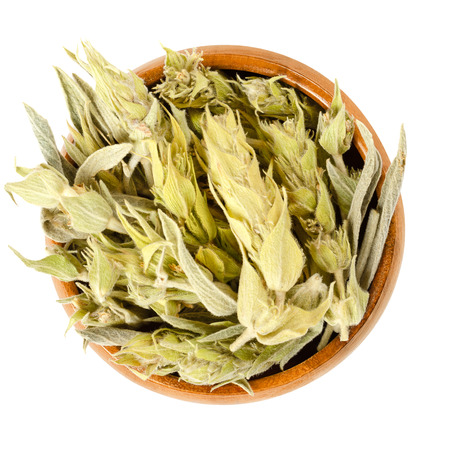 Sideritis, Greek mountain tea in wooden bowl. Also ironwort and shepherds tea. Dried flowering plants, used as herbal medicine and tea. Isolated food photo, closeup, from above, on white background.