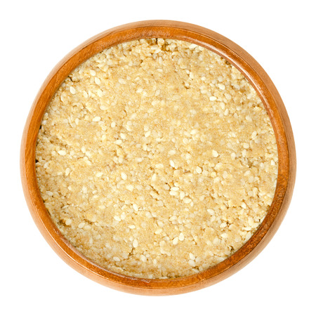 Homemade white tahini with sesame seeds in wooden bowl. Condiment made of ground husked sesame seeds. Dip or major ingredient in hummus, baba ghanoush or halva. Food photo closeup on white background. Stock Photo