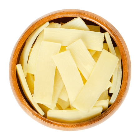 Bamboo shoots in wooden bowl. Canned slices of bamboo sprouts, used as vegetable in Asian dishes. Isolated macro food photo closeup from above on white background.