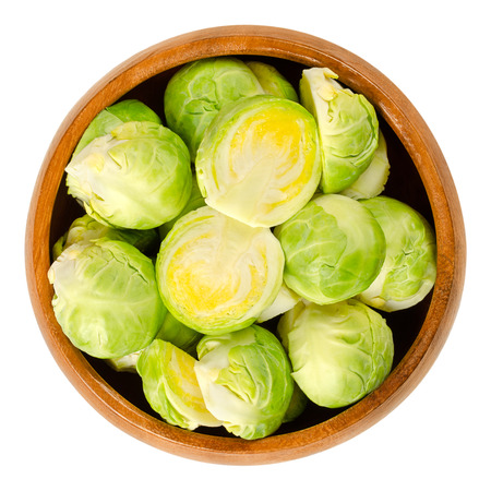 Fresh Brussels sprouts in wooden bowl. The leafy green vegetables look like miniature cabbages. Raw edible buds, member of Gemmifera group. Macro food photo, close up, from above, on white background.