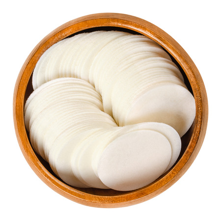 Round white wafer papers for baking in wooden bowl. Thin sheets, made of wheat flour and starch, for making cookies. Edible. Isolated macro food photo closeup from above on white background.