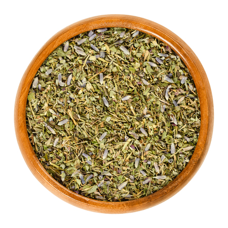 Herbes de Provence in wooden bowl. Mixture of dried herbs of the Provence, France. Savory, rosemary, thyme, lavender, oregano and marjoram. Macro food photo, closeup, from above, on white background. Stock Photo