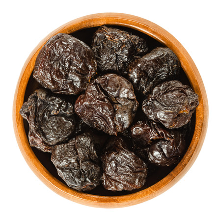 Prunes, dried plums in wooden bowl. Uncooked, dehydrated, pitted fruits of Prunus domestica with black color, used as snack. Isolated macro food photo, closeup, from above, on white background.
