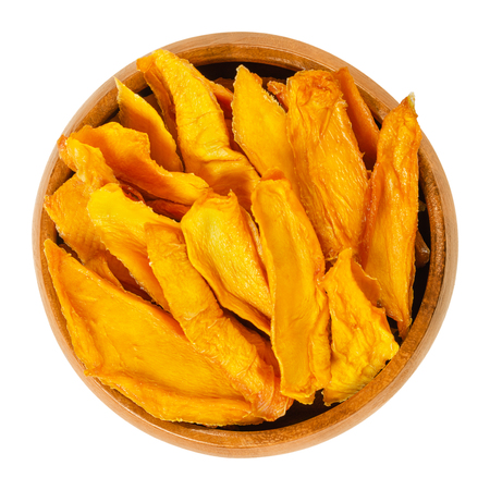 Dried mango strips in wooden bowl. Sliced, dehydrated mangoes. Juicy tropical stone fruit with yellow and orange color. Mangifera. Isolated macro food photo, closeup, from above, on white background. Stock Photo
