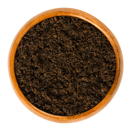 Potting soil with peat in wooden bowl. Potting mix or compost with most common ingredients turf, bark, sand and perlite. Medium to grow plants and for germination. Macro photo, closeup, over white. Stock Photo