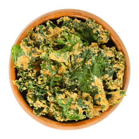 Homemade kale chips in wooden bowl. Dehydrated green leaf cabbage, coated with blended spices, nuts and vegetables. Snack and potato chip substitute. Macro food photo, closeup from above, over white.