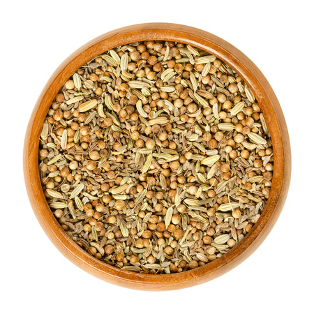 German bread spice mixture in wooden bowl. Mix of anise, fennel, coriander and caraway seeds. Used as digestive aid in bread recipes. Isolated macro food photo, closeup from above on white background.