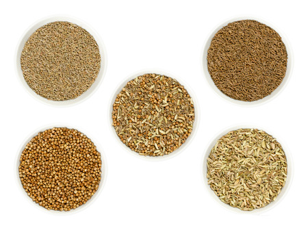 Bread spice mixture in the middle, surrounded by its single ingredients anise, caraway, coriander and fennel seeds in bowls. Dried spices to flavor bread. Photo closeup from above on white background.