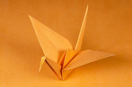 Orange origami crane on orange background. Tsuru. Japanese art of paper folding. Flat square sheet of paper transferred into a finished sculpture through folding and sculpting. Close up. Macro photo. Reklamní fotografie