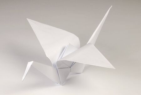 Light gray origami crane on gray background. Tsuru. Japanese art of paper folding. Flat square sheet of paper transferred into finished sculpture through folding and sculpting. Close up. Macro photo.