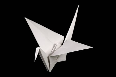 White origami crane, tsuru, on black background. Japanese art of paper folding. Flat square sheet of paper transferred into finished sculpture through folding and sculpting. Close up. Macro photo. Reklamní fotografie - 129970041