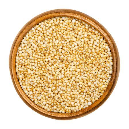 Quinua inflada en cuenco de madera. Semillas reventadas de Chenopodium quinoa, un pseudocereal, utilizado como cereales para el desayuno y en forma de tortas de arroz. Primer plano, desde arriba, sobre blanco, fotografía macro aislada de alimentos. Foto de archivo