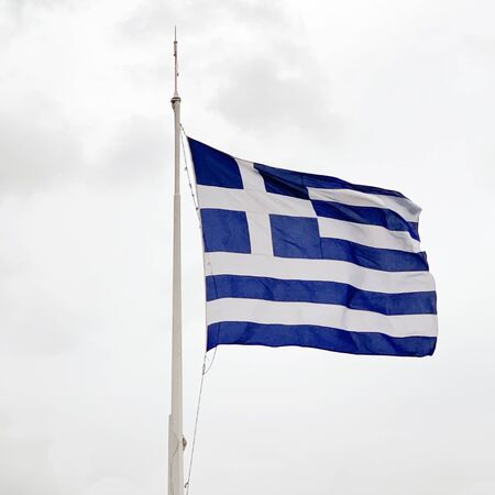 The national flag of Greece is waving on a mast in stormy weather. Also called sky blue and white. Piece of fabric and banner, used as patriotic country symbol. Nine equal alternating horizontal stripes with a white cross over a blue canton. Photo.