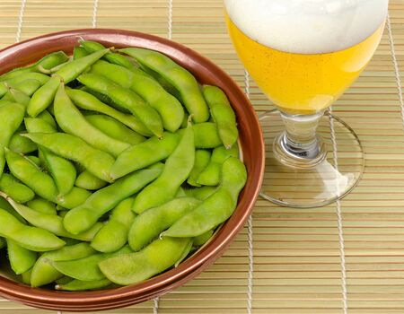 Boiled edamame in a bowl with a glass of beer on bamboo mat. Green soybeans, maodou, cooked in saltwater. Side dish and tasty snack. Soy beans, Glycine max.,protein rich legume. Closeup, food photo.