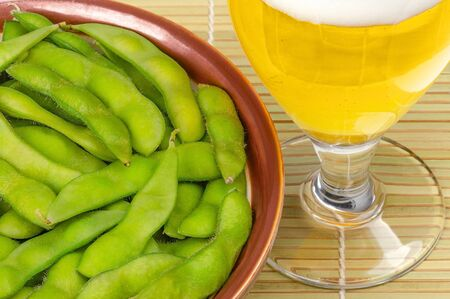Boiled edamame in brown bowl with glass of beer on bamboo mat. Green soybeans, maodou, cooked in saltwater. Side dish and tasty snack. Soy beans, Glycine max.,protein rich legume. Closeup, food photo.