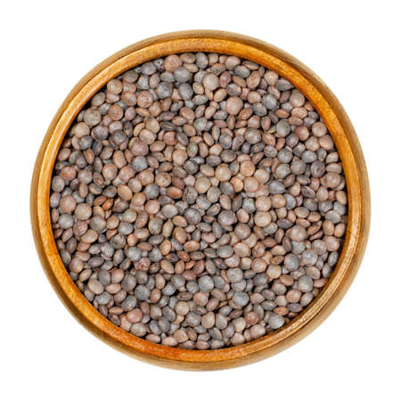 Unpeeled red lentils in wooden bowl. Dried seeds of Lens culinaris with their hulls, an edible legume, staple and a food crop. Closeup, from above, on white background, isolated macro food photo.