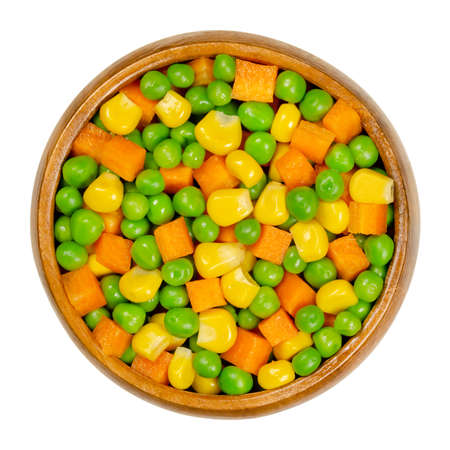 Green peas, corn and carrot cubes in wooden bowl. Mixed vegetables. Peas mixed with  vegetable maize, also called sugar or pole corn and with carrots cut in cubes. Closeup from above macro food photo. 写真素材