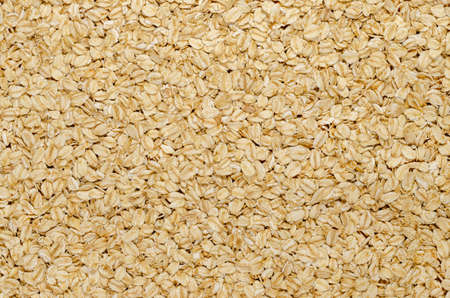 Rolled oats, surface and background. Lightly processed whole-grain food. Husked and steamed oat groats are rolled into flakes and lightly toasted to stabilize them. Food photo, top view, from above.