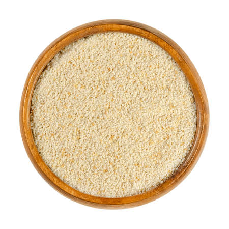 Fine breadcrumbs in a wooden bowl. Dry bread crumbs, known as breading or crispies, are sliced ​​residue of dry bread, used for breading or crumbing foods. Close-up from above, over white, food photo.