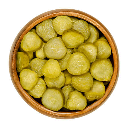 Pickled cucumber discs, also known as pickle or gherkin, in wooden bowl. Small pickled cucumbers with bumpy skin, sliced. Baby pickles. Close-up from above, over white, isolated macro food photo. Banque d'images