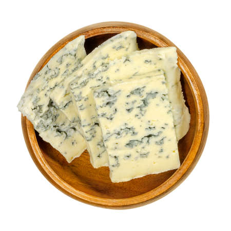 Blue cheese slices in wooden bowl. Bleu cheese made with cultures of mold Penicillium, giving it spots or veins, which can vary in color between blue and green. Close-up, from above, macro food photo. Imagens