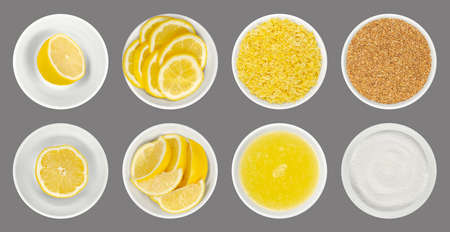 Fresh and processed lemons in white glass bowls, isolated over gray. Lemon halves, wedges and slices, freshly grated and dried lemon zest, juice and crystalline citric acid. Close up from above. Photo