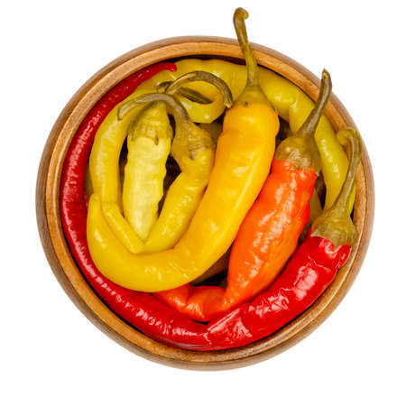 Peperoni pickles in a wooden bowl. Pickled whole chili peppers of different bright colors. Vegetable, preserved in brine. Capsicum. Close-up from above, on white background, isolated macro food photo.
