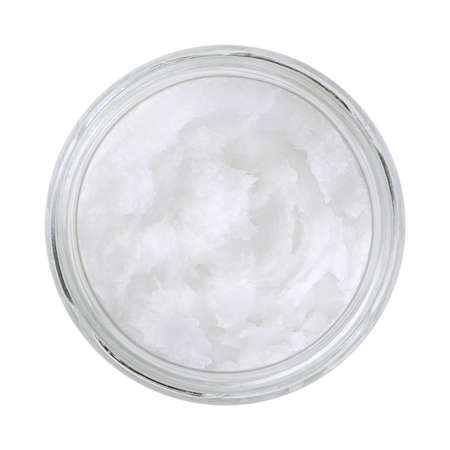 Coconut oil in a glass jar. Unrefined coconut butter, an edible oil, derived from the wick, meat, and milk of the coconut palm fruit. White solid fat, melting at warmer room temperatures. Food photo.