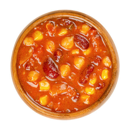 Vegetarian chili in a wooden bowl. Also chili sin carne, a spicy stew containing chili powder, tomatoes, kidney beans, chickpeas, onions, corn grains and spices. Close-up from above, macro food photo. Archivio Fotografico