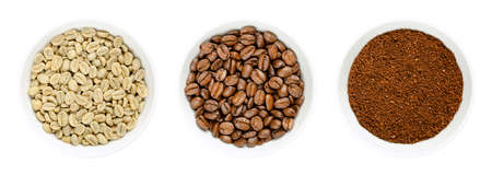 Green, roasted and ground coffee beans in white bowls. Seeds of berries from Coffea arabica, also Arabian, mountain or arabica coffee. Unroasted and roasted pits and coffee powder. Closeup food photo.
