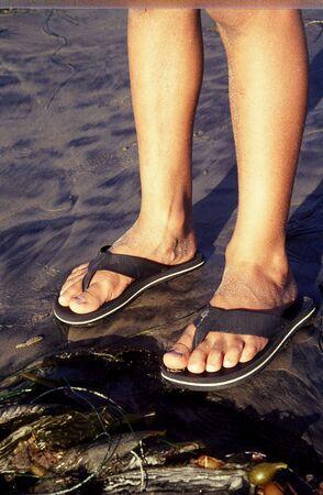 sandles: A pair of feet on the beach Stock Photo