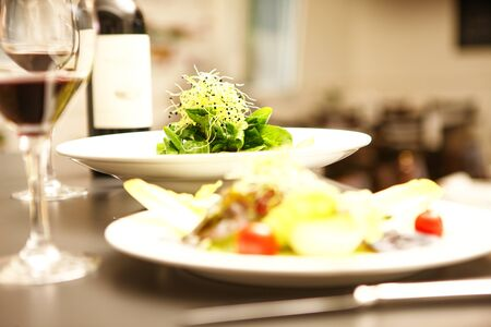 salad and red wine in a restaurant with a plate out of focus in foreground