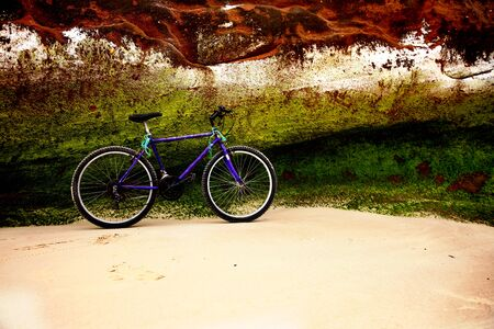 Old bike on beach with and green and rusty colored rock 版權商用圖片