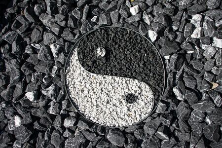 Yin and Yang designed with stone in a outdoor garden surrounding the sign