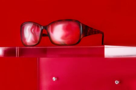glasses on a plexiglass display with red background and copy space