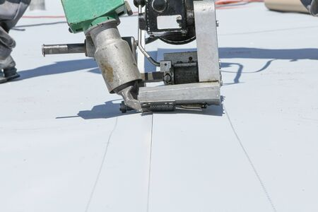 roofer joining white plastic sheets. with white roof Stock Photo