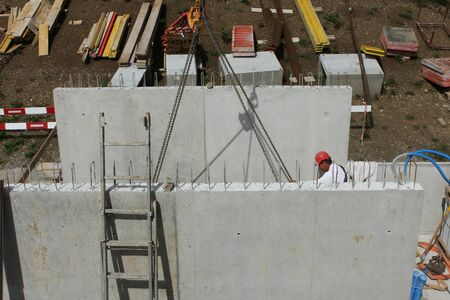 Hard working people at construction site. Worker with helmet and red pants
