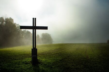 cross out in the country during a foggy morning and mystic setting with sunrise
