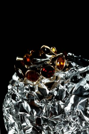 Jewelery with gem stones on tin foil black background with copy space
