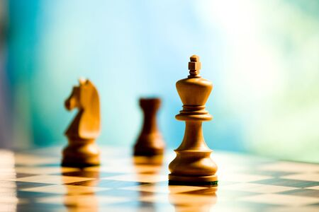 king and other players on a chess board on light blue background 版權商用圖片