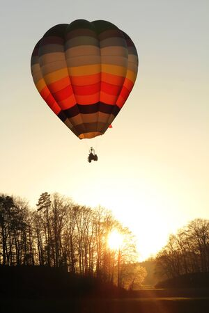 Hot air balloon above forrest and sunset