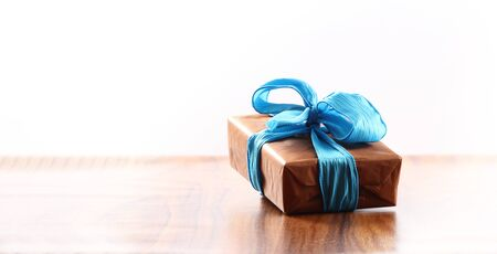 brown christmas present with ribbon. Presents in a table with decoration and copy space and a ribbon Reklamní fotografie