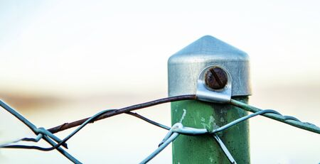 closeup of a fence pole with a rusty screw and green color in banner layout with space for copy