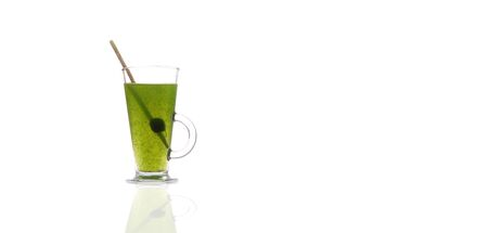 Glass with fresh wheat grass with clear water in a cup, with copy space